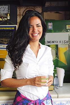 Young Brazilian woman 20 to 29 years old in a bar holding a caipirinha cocktail, Rio de Janeiro, Brazil, South America