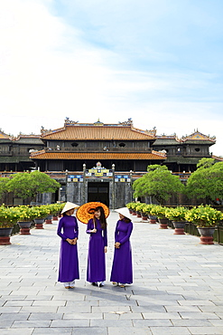 Women in traditional Ao Dai dresses with a paper parasol in the Forbidden Purple City of Hue, UNESCO World Heritage Site, Thua Thien Hue, Vietnam, Indochina, Southeast Asia, Asia