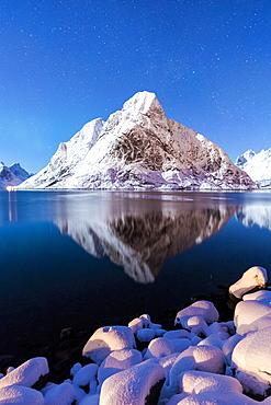 The snowy peaks are reflected in the frozen sea on a starry winter night, Reine Bay, Nordland, Lofoten Islands, Arctic, Norway, Scandinavia, Europe