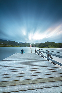 Hiker on wooden deck admires the sea illuminated by blue lights at night, Holdalsvatnet, Vestvagoy, Lofoten Islands, Norway, Scandinavia, Europe
