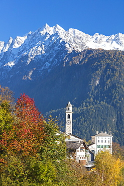 The colorful trees frame the alpine church and the snowy peaks, Soglio, Bregaglia Valley, Canton of Graubunden, Swiss Alps, Switzerland, Europe