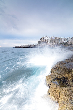Waves of turquoise sea crashing on cliffs framed by the old town, Polignano a Mare, Province of Bari, Apulia, Italy, Europe