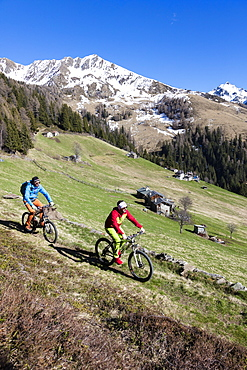 Mountain bikes on green meadows framed by snowy peaks in spring, Albaredo Valley, Orobie Alps, Valtellina, Lombardy, Italy, Europe