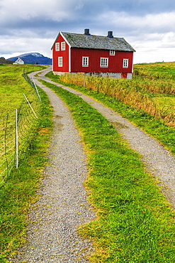 Red wooden house and country road in Flakstad, Lofoten Islands, Norway, Europe