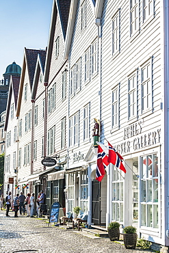 Norwegian flags hanging from white wood buildings and shops, Bryggen, Bergen, Hordaland County, Western Fjords region, Norway, Scandinavia, Europe
