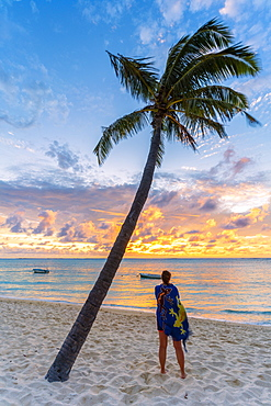 Rear view of woman with sarong admiring the ocean at sunset on palm-fringed beach, Le Morne Brabant, Black River, Mauritius, Indian Ocean, Africa