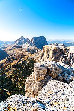 Paragliding over Sassolungo, Sassopiatto and Sella Pass in autumn seen from Sass Pordoi, Dolomites, Trentino, Italy, Europe