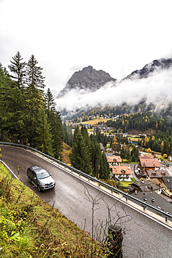 Car travelling on mountain road towards the village of Canazei in autumn, Dolomites, Val di Fassa, Trentino-Alto Adige, Italy, Europe