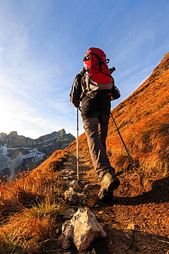Hiker proceeds toward the group Forcella De Furcia at sunrise, Funes Valley, South Tyrol, Dolomites, Italy, Europe