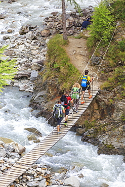 Hikers cross the wooden bridge on a creek in the woods, Minor Valley, High Valtellina, Livigno, Lombardy, Italy, Europe