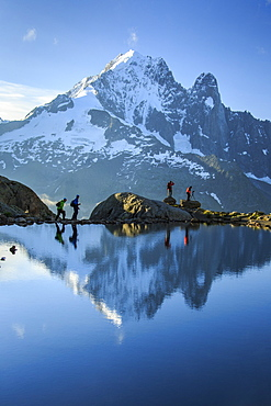 Hikers on the shores of Lac de Cheserys, with Aiguille Verte reflected at dawn, Chamonix, Haute Savoie, French Alps, France, Europe