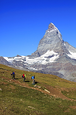 Hikers proceed with the Matterhorn in background in a clear summer day, Gornergrat, Canton of Valais, Swiss Alps, Switzerland, Europe