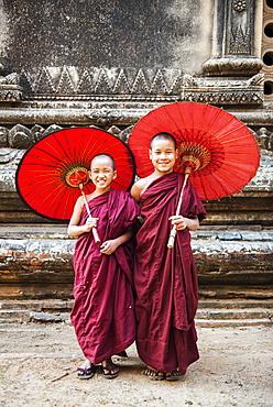 Two young monks and traditional umbrellas, Bagan (Pagan), Myanmar (Burma), Asia