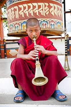 Monk playing lingum trumpet in front of a prayer wheel, Punakha, Bhutan, Asia