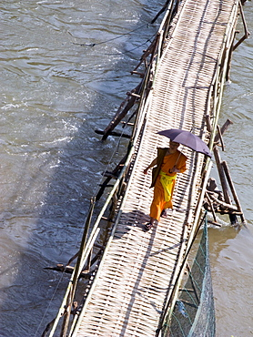 Laos, monk crossing the river in the holy city of luang prabang