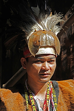 Man in traditional native Iban costume in a longhouse in Borneo, Malaysia, Southeast Asia, Asia