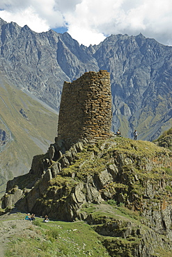 Tourists trekking by a tower near the Gergeti Holy Trinity Church by the river Chkheri, under Mount Kazbegi at an elevation of 2170 meters in the Caucasus, Georgia, Central Asia, Asia
