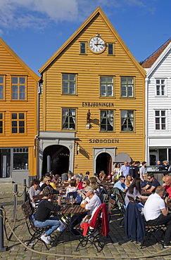 Tourists sit in the sun in outdoor bars and cafes in the old wharf and traditional wooden buildings in the Bryggen quarter of Bergen, Norway, Scandinavia, Europe
