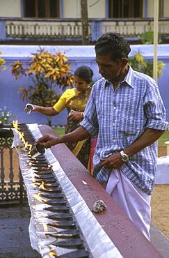 India: religion - christian lighting oil lamps. Valiapally catholic church, kerala