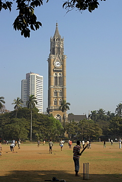 India cross maidan with cricket game, old and new buildings in background, mumbai.