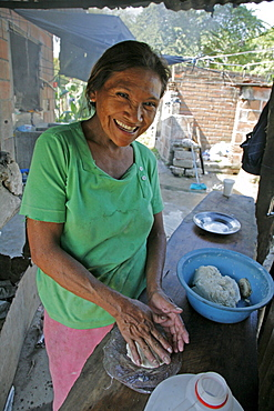 Honduras woman making tortillas. slum barrio of chamelecon, pedro sula