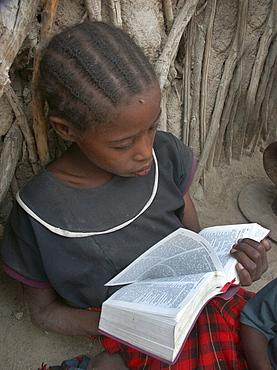 Watatulu girl reading bible, tanzania. Mwankale