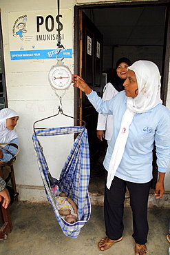 Indonesia growth monitoring (baby weighing) at a posyandu, or mother-child temporary health post in village of paya lumpat. Photograph taken in meulaboh, aceh province -december 2006, 2 years after tsunami of december 26th 2004 devastated much of coastal region. Taken to illustrate reconstruction work projects of (catholic relief services) of sponsored photo tour