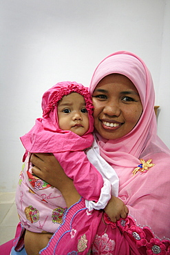 Indonesia mother child built in banda aceh by. Photograph taken in banda aceh, -december 2006, 2 years after tsunami of december 26th 2004 devasted much of coastal region. Taken to illustrate reconstruction work projects of (catholic relief services) of sponsored photo tour