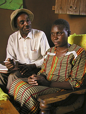 Social worker (left) visiting blind woman with aids, tanzania. Musoma