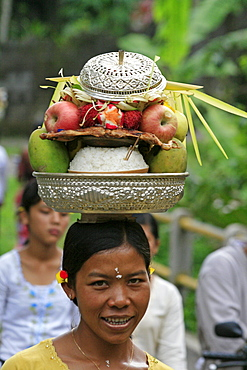 Indonesia woman walking along road carrying food offerings to temple, on hedr head, during hindu ceremony near klungkung on full moon. Bali