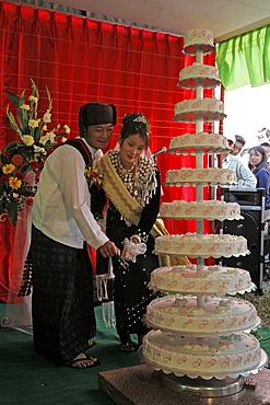 Myanmar bride groom cutting cake, catholic wedding of tribal kachins at myitkyina, a largely kachin community in north burma near chinese border