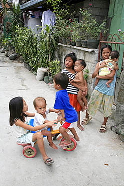Philippines children playing in the street of the slum of bagnong silangan, quezon city, manila