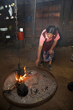 Chile. Mapuche woman heating water in her kitchen, temuco
