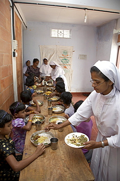 India. Sister bincy joseph aruviyil serving, during mealtime at the mary matha bala bhavan, a girls orphanage run by syro-malabar catholic missionary sisters of mary immaculate (msmi), chamal village, thamarassery diocese, khozikode, kerala. 2007