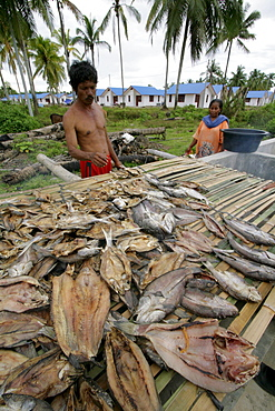 Indonesia crs housing project at seunebok tuengoh relocation site. zaman, a fisherman, smoking fish. meulaboh, aceh, two years after the tsunami