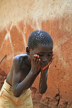 Burundi family of speciose ciza (32) and three children, claude (9), constantin (6) and orave (1). Claude washing his face. Giteraa.