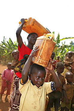 Burundi woman and her son carrying water from a stand pipe located 300 metres from their home.