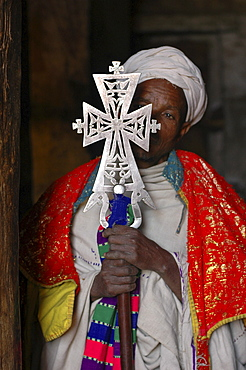 Religion, ethiopia. Geneta maryam, a church 31 kms from lalibela, built around 1270 by yekuno amlak. Priest at the church holding an ancient cross