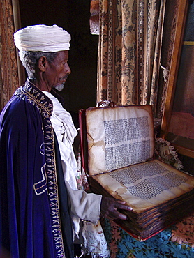 Religion, ethiopia. Priest at church of saints gabriel and rafael, lalibela, with an ancient parchment book