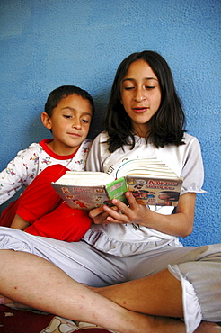 Colombia day in the life series: hugo andres, 7, of ciudad bolivar, bogota, being read to by his sister lineth