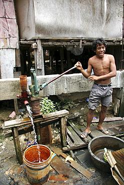 Thailand slum dweller pumping water, chiang mai