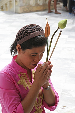 Thailand woman praying while she holds a lotus flower, ancient buddhist temple and stupa of phra pathom chedi, nakhon pathom