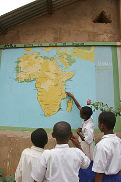 Tanzanian school children point out their country on the map of africa on the wall of their school