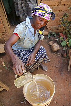 Tanzanian woman with unsafe drinking water collected in a bucket from a stream near her home. The water is contaminated with amoebas and other parasites. Kighare, same, in the north-east near kilimanjaro
