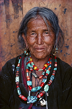 Torpu eppi. Every line in work-worn face tells a story. In mountains, is a sign of wisdom in of survival. Torpu eppi wears heirloom necklaces of coral, amber, turquoise, acquired on trading trips to tibet humla, north-west nepal
