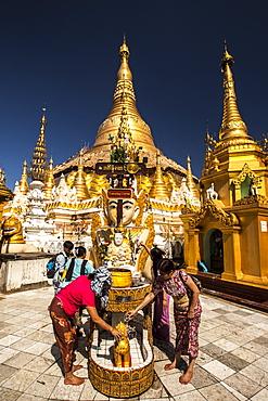 Water offering at Tuesday Corner statue, Shwedagon Paya, Yangon (Rangoon), Myanmar (Burma), Asia