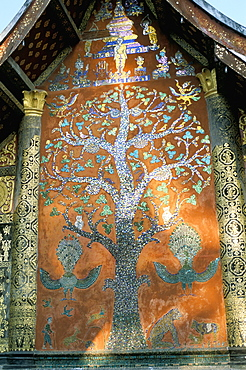 Glass mosaic of tree of life on wall of the 16th century Sim, Wat Xiang Thong, Luang Prabang, UNESCO World Heritage Site, Laos, Indochina, Southeast Asia