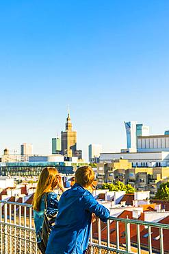 Couple looking at Palace of Culture and Science and skyscrapers, City Centre, Warsaw, Poland, Europe