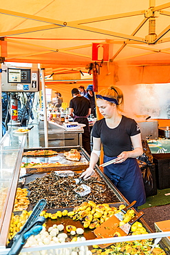 Vendor cooking on grill at market in Helsinki, Finland, Europe