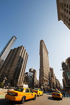 Flat Iron Building and yellow cabs at the intersection of 5th Avenue and Broadway, New York, United States of America, North America